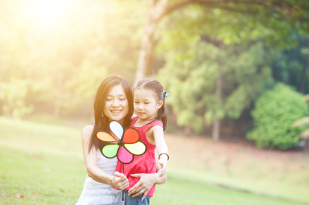 fun in the sun: Love between mother and daughter. Asian family outdoor fun, morning with sun flare.