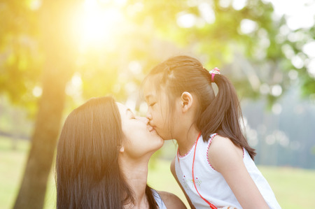 outdoor outside: Lifestyle portrait mom and daughter kissing in happiness at the outside in the park. Family outdoor fun, morning with sun flare.
