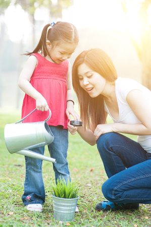 fun in the sun: Asian mother and daughter are exploring nature and having fun. Family outdoor fun, morning with sun flare.