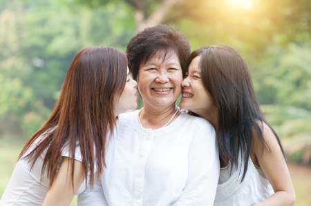 Portrait of beautiful Asian daughters kissing elderly mother, senior adult woman and grown child. Outdoors family at nature park with beautiful sun flare. Foto de archivo