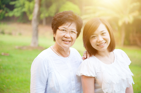 Portrait of attractive Asian elderly mother and daughter, senior adult woman and grown child. Outdoors family at nature park with beautiful sun flare.