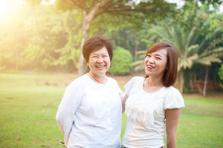 Porträt der asiatischen älteren sprechenden Mutter und Tochter, ältere erwachsene Frau und gewachsenes Kind. Draußen Familie am Naturpark mit schönen Sonneneruption. Standard-Bild - 75646553