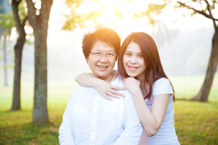 Portrait of Asian elderly mother and daughter, senior adult woman and grown child. Outdoors family at nature park with beautiful sun flare. Stock Photo