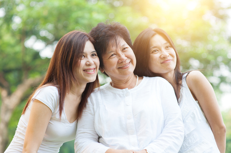 Portrait of happy Asian elderly mother and her daughters, senior adult woman and grown child. Outdoors family at nature park with beautiful sun flare. Stock Photo