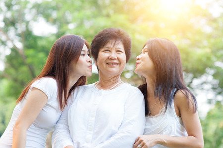 Portrait of happy Asian daughters kissing elderly mother, senior adult woman and grown child. Outdoors family at nature park with beautiful sun flare.