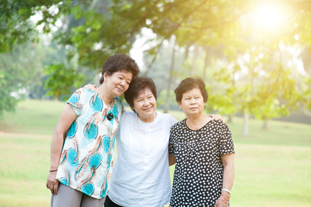 fun in the sun: Group of Asian elderly women having fun at green park, active senior adult outdoors, friendship concept, morning sun flare background. Stock Photo