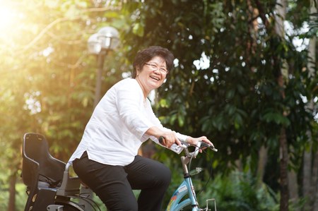 Active elderly Asian woman cycling, senior adult activity, riding bike outdoor in morning. Banque d'images