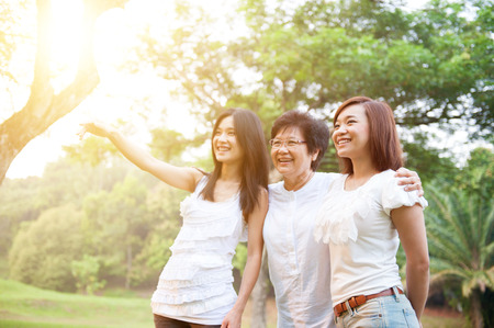 three generations of women: Portrait of Asian elderly mother and daughters pointing looking away, senior adult woman and grown child. Outdoors family at nature park with beautiful sun flare. Stock Photo