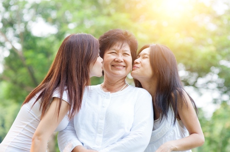 Portrait of Asian daughters kissing elderly mother, senior adult woman and grown child. Outdoors family at nature park with beautiful sun flare. Foto de archivo