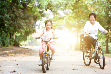 Portrait of active multi generations Asian family at nature park. Grandmother and granddaughter riding bicycle outdoor. Morning sun flare background.