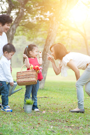 Candid portrait of happy multi generations Asian family at nature park. Grandmother, mother and children outdoor fun. Morning sun flare background.