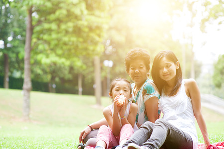 Portrait of multi generation Asian family at nature park. Grandmother, mother and daughter outdoor fun. Morning sun flare background. Stock Photo