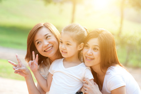 Asian family portrait at nature park, morning outdoor with sun flare. photo