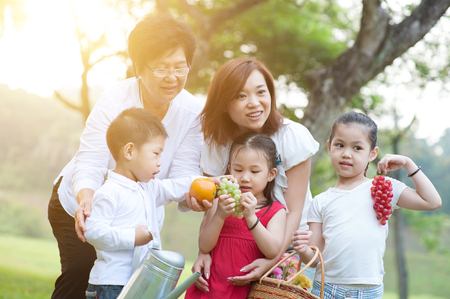 Candid portrait of joyful multi generations Asian family at nature park. Grandmother, mother and grandchildren outdoor fun. Morning sun flare background. photo