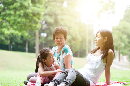 Candid portrait of multi generation Asian family at nature park. Grandmother, mother and grandchild outdoor fun. Morning sun flare background. Stock Photo