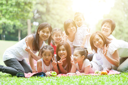Cheerful Asian multi generations family portrait, grandparent, parents and children, outdoor nature park in morning with sun flare. photo