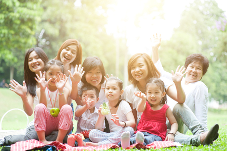 Group of Asian multi generations family portrait, grandparent, parents and children, outdoor nature park in morning with sun flare. photo