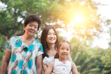 Portrait of happy multi generations Asian family at nature park. Grandmother, mother and daughter outdoor fun. Morning sun flare background.