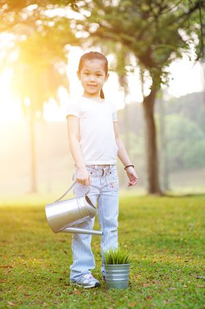 fun in the sun: Portrait of active Asian kid watering plant outdoors. Little girl having fun at nature park. Morning sun flare background.