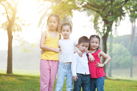 Portrait of four Asian children at park. Little girls and boy having fun outdoors. Morning sun flare background. photo