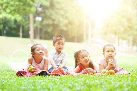 Portrait of Asian children picnics at park, lying on lawn. Little boy and girls having fun outdoors. Morning sun flare background. photo