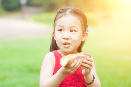 Portrait of Asian kid eating sandwich at park. Little girl having fun outdoors. Morning sun flare background. photo
