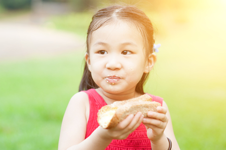 Portrait of Asian child eating sandwich at park. Little girl having fun outdoors. Morning sun flare background. photo
