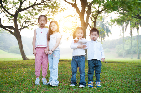 Portrait of Asian children at park. Kids having fun outdoors. Morning sun flare background. photo