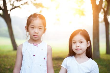 fun in the sun: Portrait of Asian children at park. Little girls having fun outdoors. Morning sun flare background. Stock Photo