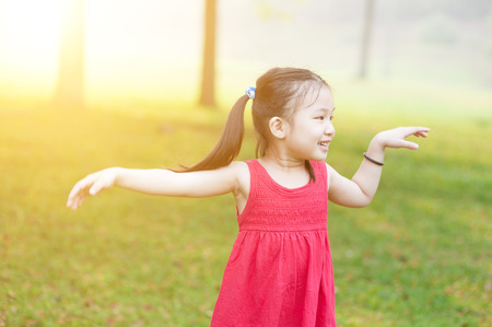 Portrait of active Asian child dancing outdoors. Little girl having fun at nature park. Morning sun flare background. photo
