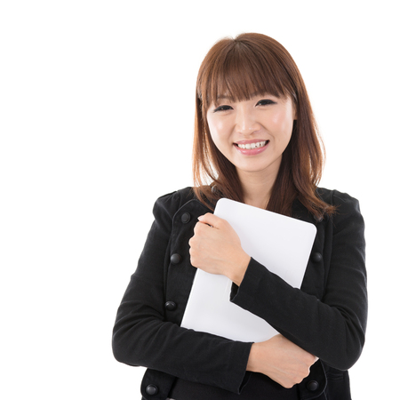 Young Asian woman holding digital computer tablet and smiling, isolated on white background. photo