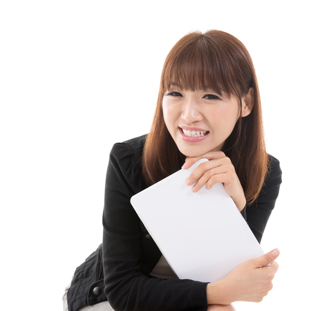 Young Asian girl holding digital computer tablet and smiling, isolated on white background. photo