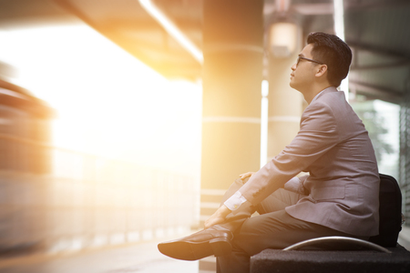 Asian businessman sitting at railway station, waiting for train, beautiful sun light at background.