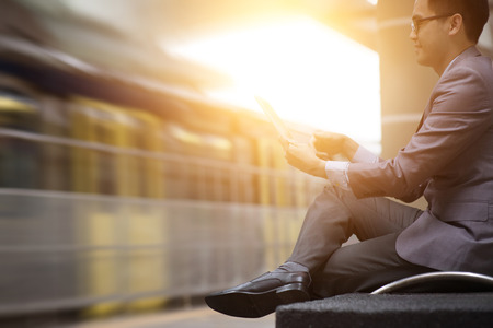 Asian businessman using digital tablet pc at railway station, with beautiful sun flare at background.