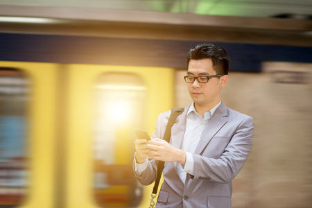 Asian businessman texting using smartphone while waiting train at railway station.