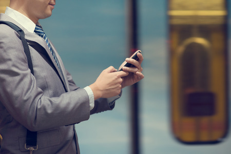 internet terminal: Business people hand using smart phone in subway station, train passing by at the background. Stock Photo