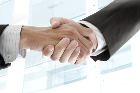 Close up businessmen handshake with modern skyscrapers as background. photo