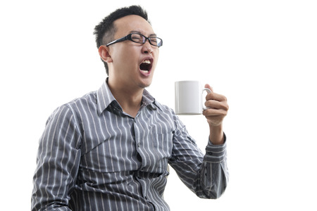 Yawning Asian male holding a cup of coffee isolated on white background photo