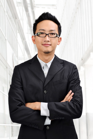 Asian businessman in full suit standing in front modern building. photo