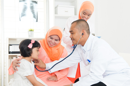 Southeast Asian child patient consulting medical doctor. Muslim family.  스톡 콘텐츠