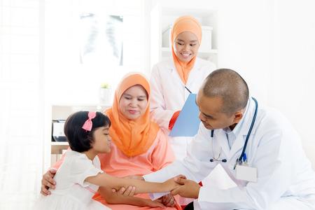 Patient-enfant d'Asie du Sud-Est consultant en médecine. Famille musulmane. Petite fille avec un bras cassé faisant un bilan de santé. Banque d'images - 81474792