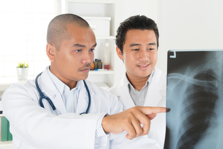 Doctors analyzing x-ray together in medical office. Southeast Asian Muslim people.