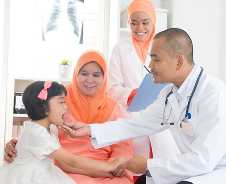 Southeast Asian male doctor examining little girl patient. Muslim medical concept. photo