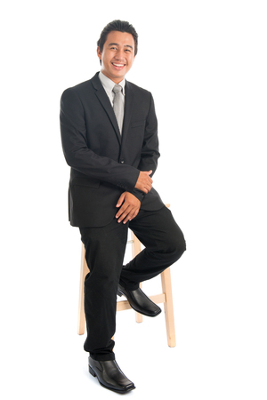 Full body portrait of young Southeast Asian businessman sitting on high chair, isolated on white background.