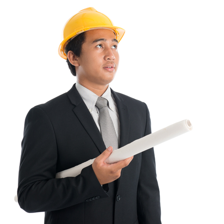 industry: Portrait of attractive Southeast Asian engineer with yellow hard hat holding blue prints and looking away, standing isolated on white background. Stock Photo