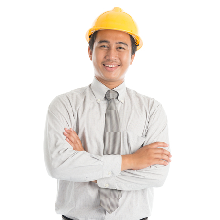Portrait of attractive Southeast Asian engineer with yellow hard hat arms crossed smiling, standing isolated on white background.