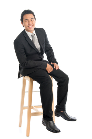 Full body portrait of attractive young Southeast Asian businessman sitting on high chair, isolated on white background.