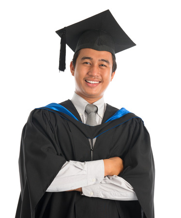 Waist up happy Asian male university student in graduation gown smiling, isolated on white background. Good looking Southeast model. Stock Photo