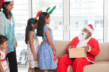 cute guy: Happy Indian family celebrating Christmas holidays, with gift box and santa at home, Asian people festival mood indoors.