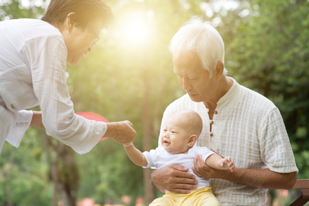 Baby grandson and grandparents having fun outdoors. Asian family, life insurance concept.